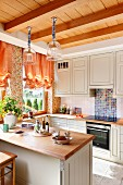 Pale, country-house-style kitchen with breakfast bar below pendant lamps hanging from wooden ceiling
