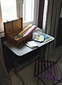 Craft utensils in open vintage suitcase on metal table and purple folding chair below window