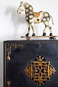 Old toy horse on castors on radiator cover with antique brass ornamentation