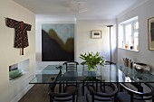 Dining table with glass top and 20s-style armchairs; kimono used as wall hanging and modern artwork in background