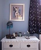 Art Nouveau table lamp and candlestick on white lace tablecloth on top of rustic chest of drawers against wall painted pastel lilac