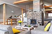 Gelbe Kissen auf Polstersofa mit graumeliertem Stoffbezug und Bodentisch vor Kaminofen in Gabionenwand, in ausgebautem Dachgeschoss hellgrau getönt
