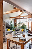 Dining area with wooden table, and lounge area with grey sofa set in open-plan interior with exposed wooden structure