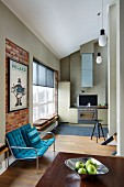 Bench with blue seat cushions against brick wall in front of modern fitted kitchen in open-plan interior