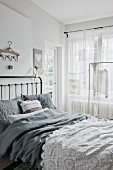 Bed with grey bed linen and white crocheted blanket