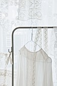 Lace top hanging from clothes rack in front of lace curtain