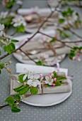 Apfelblüten mit Besteck und Papierrollen mit Namen