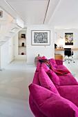 Magenta Couch in modernem, offenem Wohnraum, im Hintergrund Schreibtisch und Klassikerstuhl