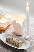 Take-away carton, tealights in paper cups, lit candle in glass and Swiss roll