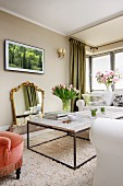 Delicate coffee table with rustic wooden top on long-pile rug, vases of flowers and gilt-framed mirror on wall in classic living room