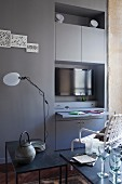 Fitted cupboards in niche with pull-out desk and TV