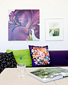 Drinking glass and open book on table in front of sofa with patterned scatter cushions below pictures on wall