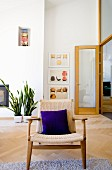 Fifties-style armchair with woven back and seat in modern interior