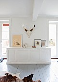 White, custom-made sideboard, framed pictures and hunting trophy in minimalist country-house interior with wooden floor