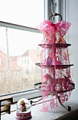 Toy figurines on vintage cake stand with pink lace ribbon on windowsill