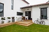 Modernes Wohnhaus mit rustikaler Holzterrasse, Rasen und Fahrrad