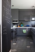 Elegant, grey kitchen with glossy fronts, accent floor tiles, U-shaped counter and writing on blackboard wall