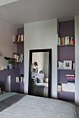 Angelehnter schwarz gerahmter Wandspiegel zwischen offenen mauvefarbenen Bücherregalen im Schlafzimmer