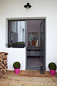 Elegant entrance area; box balls in pink pots flanking outside door and rustic stack of firewood on wooden terrace
