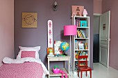 Girl's bedroom with mauve-painted walls, open-fronted shelves and pink standard lamp