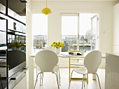 White shell chairs and yellow Tripp Trapp chair in front of French windows
