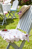 Romantic floral seat cushion on pale grey garden chair decorated with dish of strawberries and sun hat