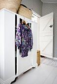 Kleiderbügel mit geblümtem Kleid an weißem Kleiderschrank aufgehängt, im Schlafzimmer mit gemusterter Tapete an Wand