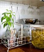 Retro glassware in white wire basket next to glass jar of elderflower syrup