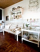 Serving trolley next to white bench with scatter cushions and bolsters against wainscoting in rustic interior with mosaic parquet floor