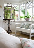 Vintage bird cage with ornate metal stand next to white bench in wood-clad conservatory