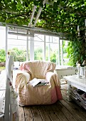 Comfortable armchair on wooden floor in front of white-painted wooden lattices with roller blinds on veranda with climber-covered pergola
