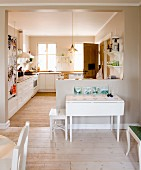 View from dining area into open-plan, rustic kitchen with white folding table against half-height partition