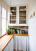 Fitted cabinet with glass doors above wooden worksurface with white curtains below in pantry