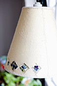Pale fabric lampshade decorated with pattern of violas