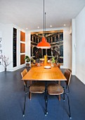 Extendible table, retro school chairs and orange pendant lamps in front of large painting in dining area