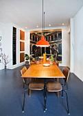 Ausziehtisch mit Retro Schulstühlen und orangefarbenen Pendelleuchten vor großformatigem Gemälde im Essbereich
