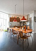 Retro kitchen with spacious dining area and orange pendant lamps in renovated town-house apartment