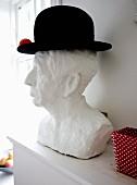 weiße männliche Gipsbüste mit schwarzem Hut dekoriert