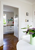 Vase of flowers on white table and view into modern kitchen through open doorway with continuous herringbone parquet flooring