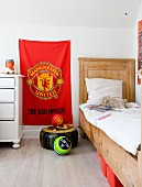 Rustic wood-framed bed with tall headboard next to red Manchester United flag hung on wall in boy's bedroom