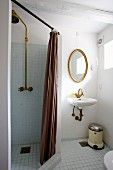 Separate shower area with brown curtain and sink below gilt-framed oval mirror to one side
