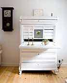 White-painted bureau with lit candles in brass candlesticks on folded-down desk in rustic interior