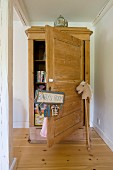 Pale wooden farmhouse cupboard with open door, sign hanging from doorknob and hobby horse to one side