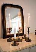 Still-life arrangement of lit candles in vintage crass candlesticks in front of mirror