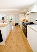 Kitchen counter with white base units and free-standing counter in kitchen with wooden floor
