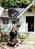 Kleines Mädchen auf Schaukel aus Weidenzweigen, im Hintergrund weisses Holzhaus