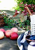 Red apples and crockery on rustic table outdoors