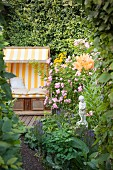 Flowering lily and rose bush in front of secluded seating area with yellow and white striped beach chair in idyllic garden