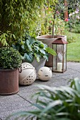 Ornamental spheres and lanterns on paved area in garden in front of bamboo bush
