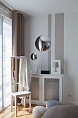 Convex mirrors above radiator cover in bedroom with valet stand